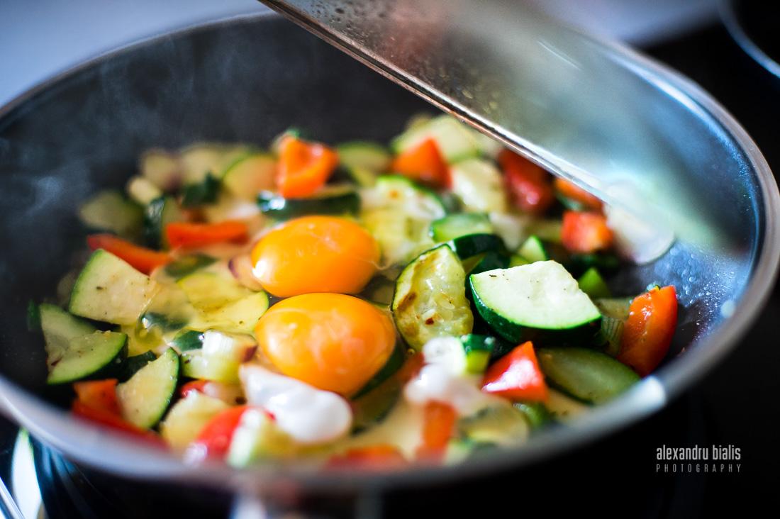 Fotografie culinara, zucchini, oua ochi, ardei rosu, ceapa verde in tigaie, gatite al dente