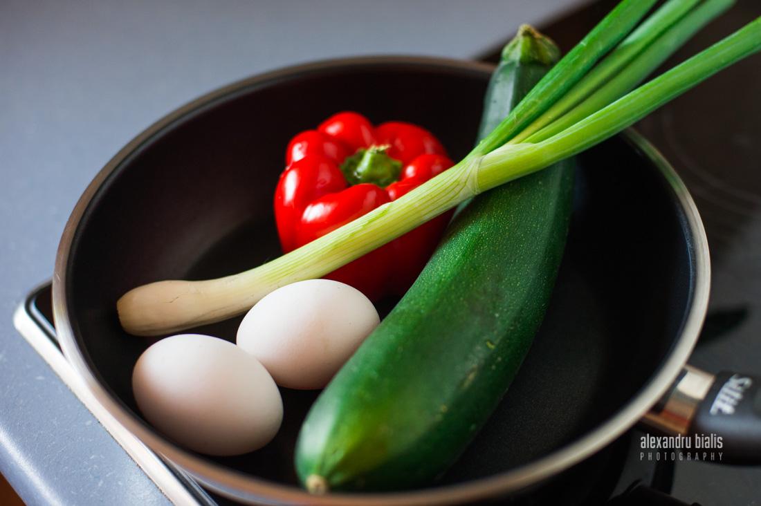 Fotografie culinara, zucchini, oua crude, ardei rosu, ceapa verde in tigaie